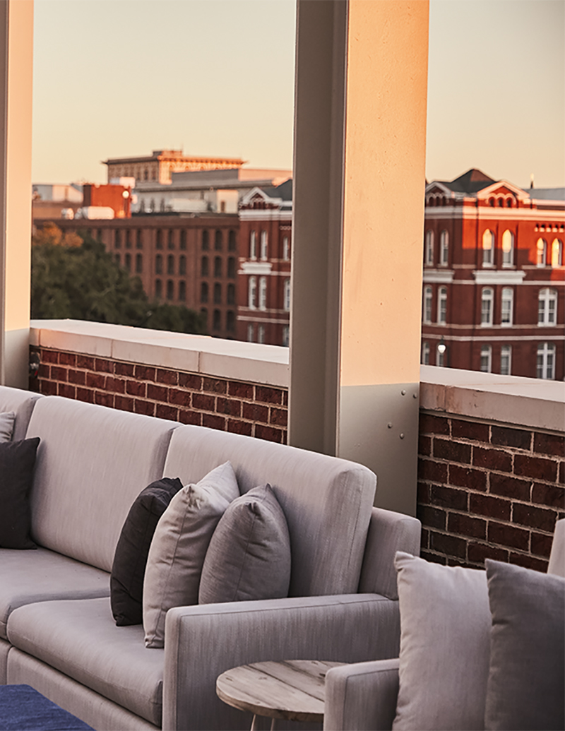 Sofa on rooftop terrace with view of buildings