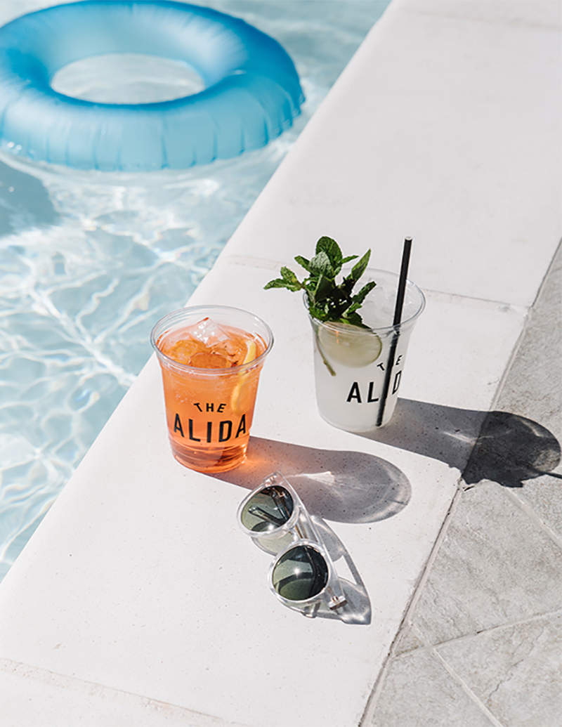 Sunglasses, drinks sitting next to pool, and floating tube in pool