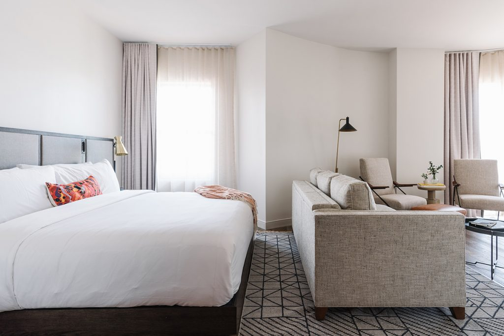Hotel room with bed that faces a living room area with sofa and chairs